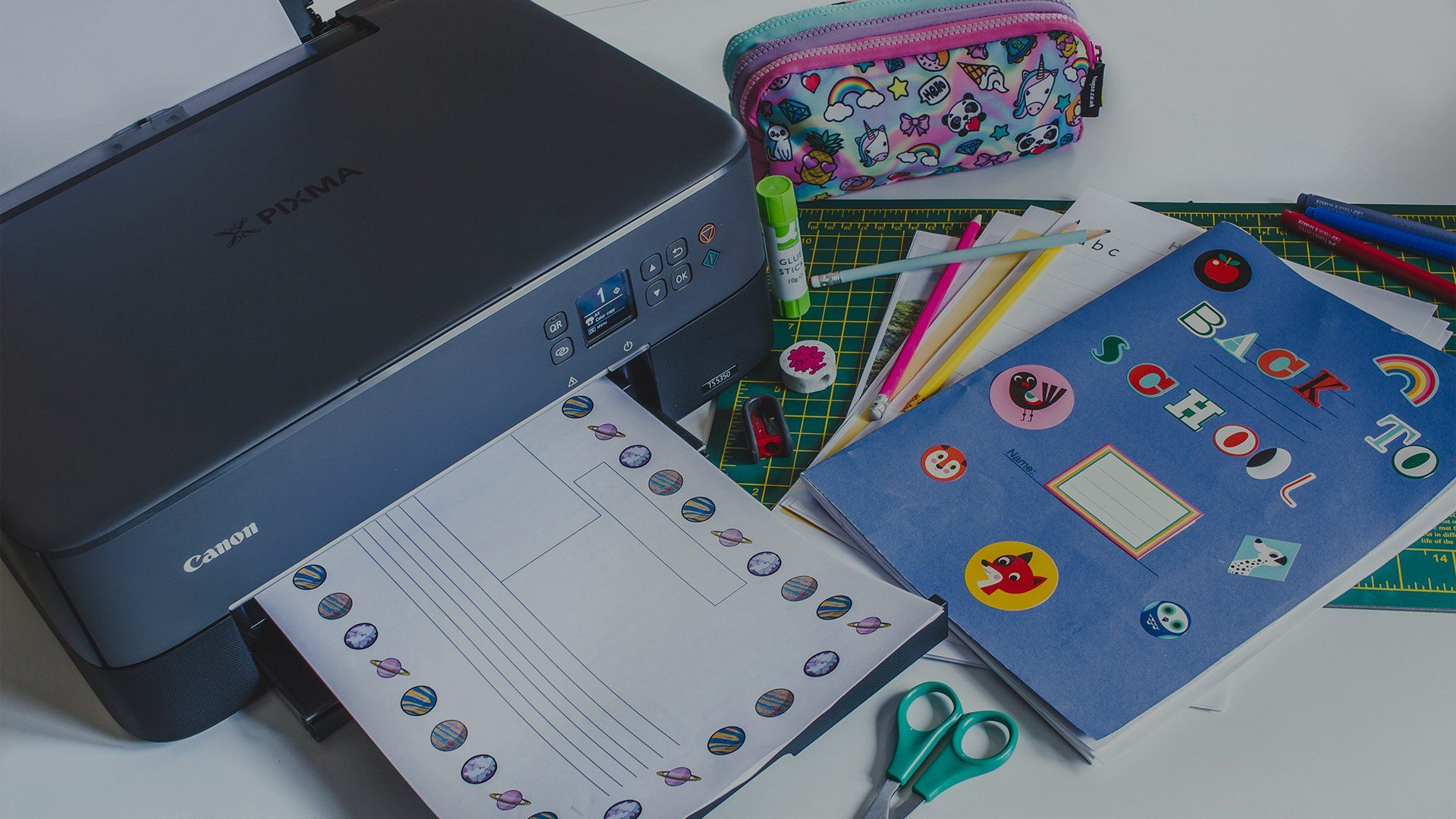 A Canon PIXMA TS5340 printer next to school books, a pencil case and a pair of scissors.